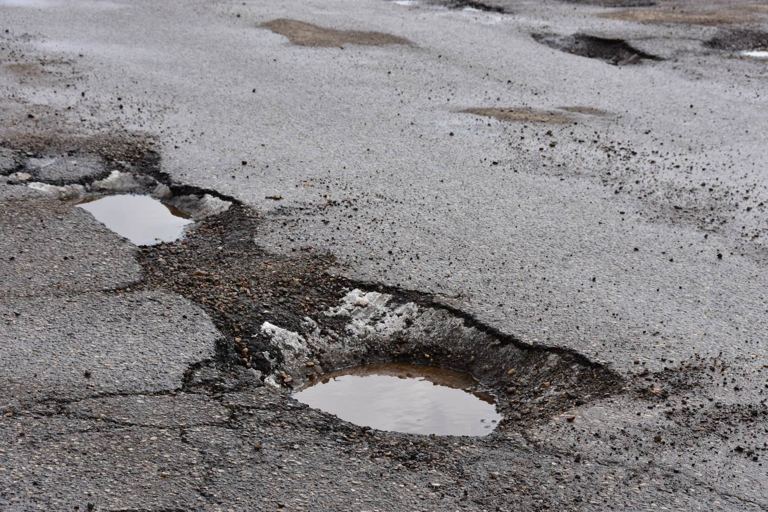 Large potholes with small puddles in them