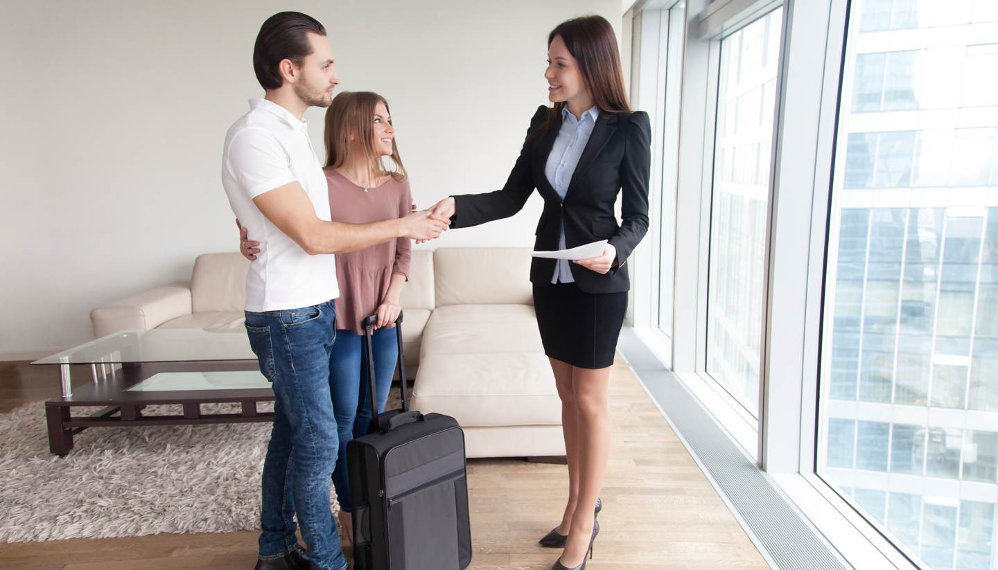 A woman shaking hands with potential tenants