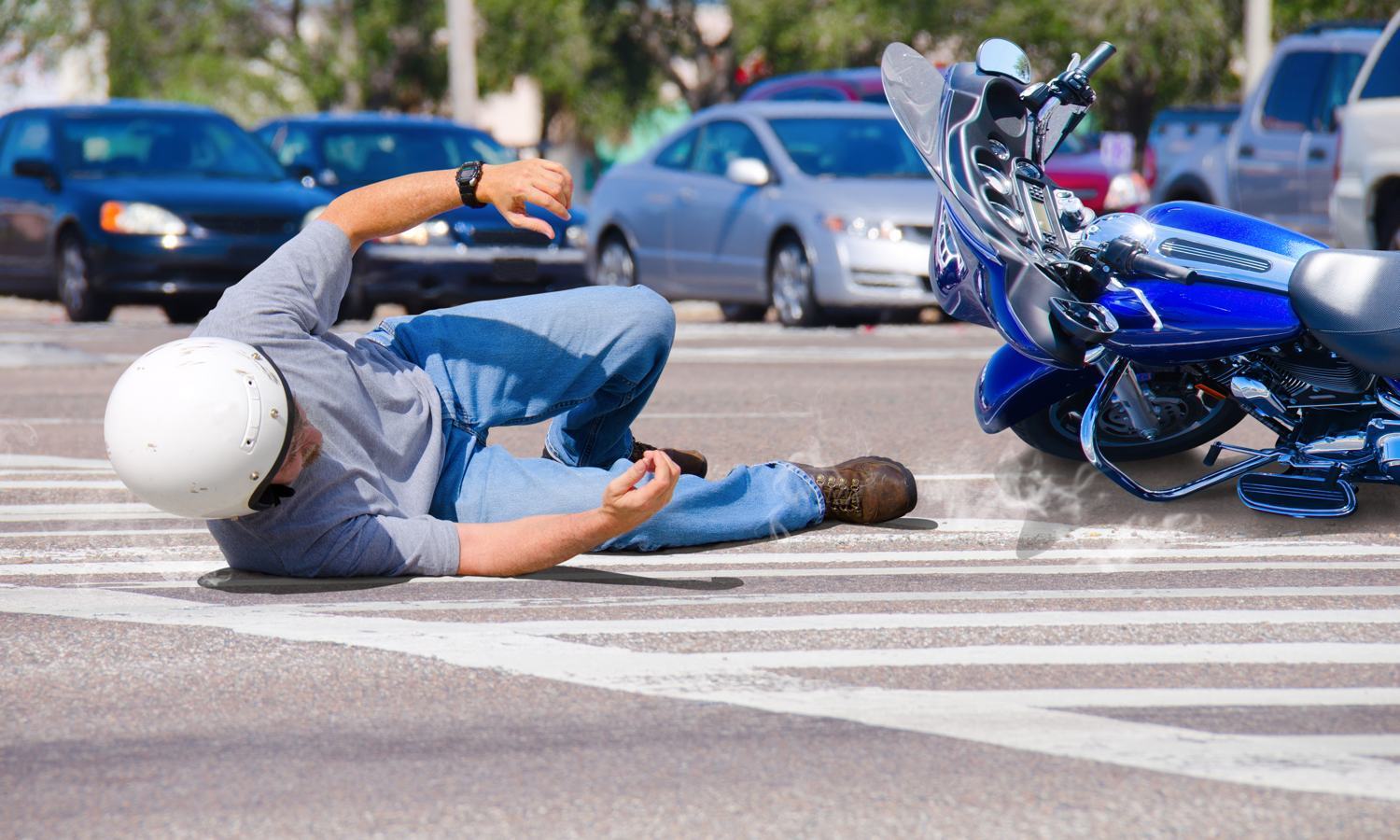 Man on the floor in a motorcycle accident with a car