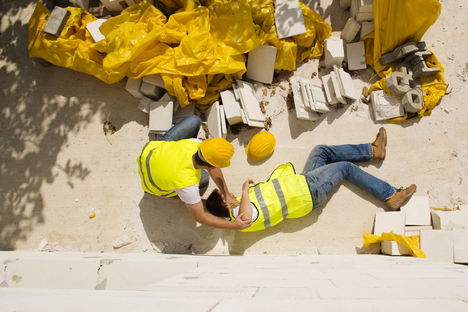 Injured construction site worker lying on ground, co-worker attending to him