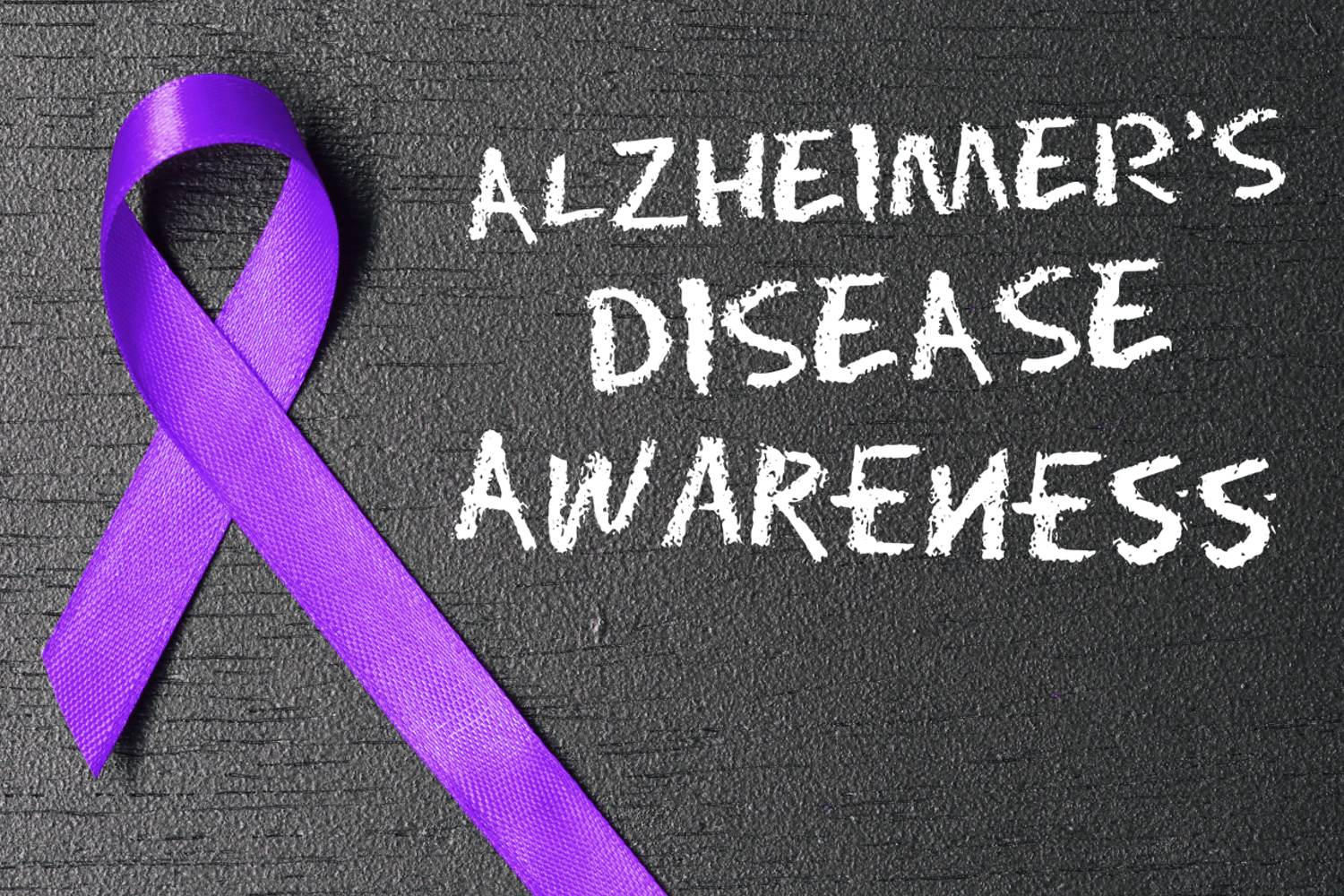 Alzheimer's Disease Awareness written on a chalk board with white chalk. Purple ribbon on left hand side