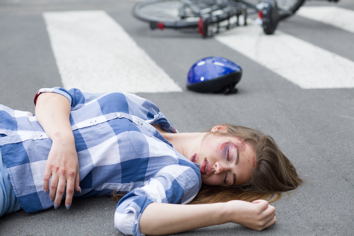 Young woman lying hurt on the road with her bike and helmet at the background