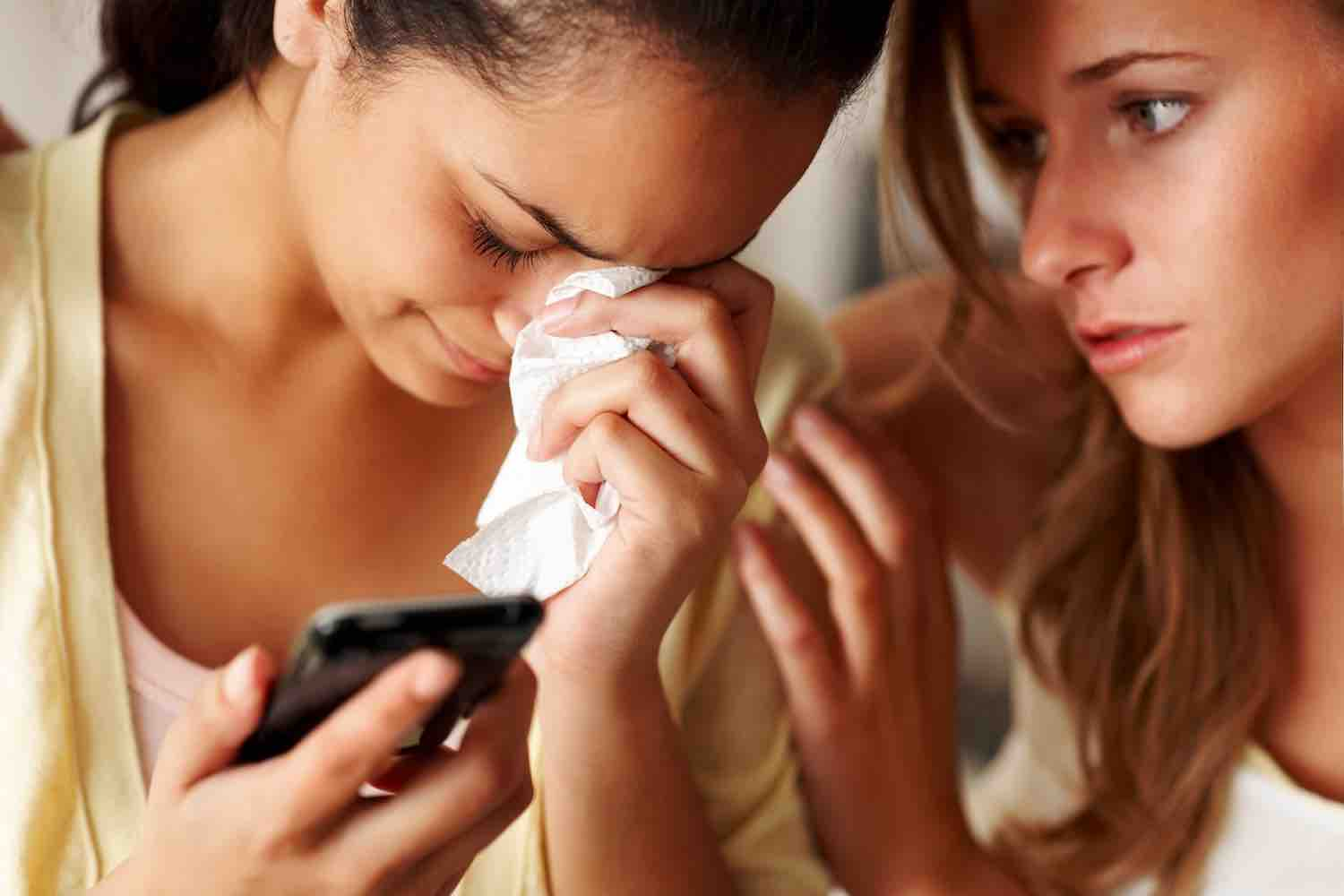Closeup portrait of a woman crying holding a mobile phone with a friend consoling her