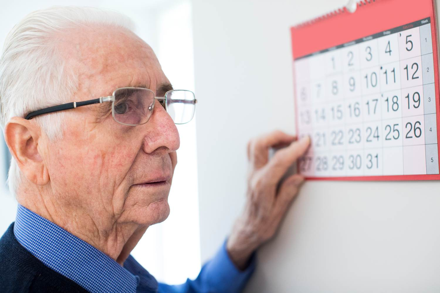 Elderly man looking confused at calendar